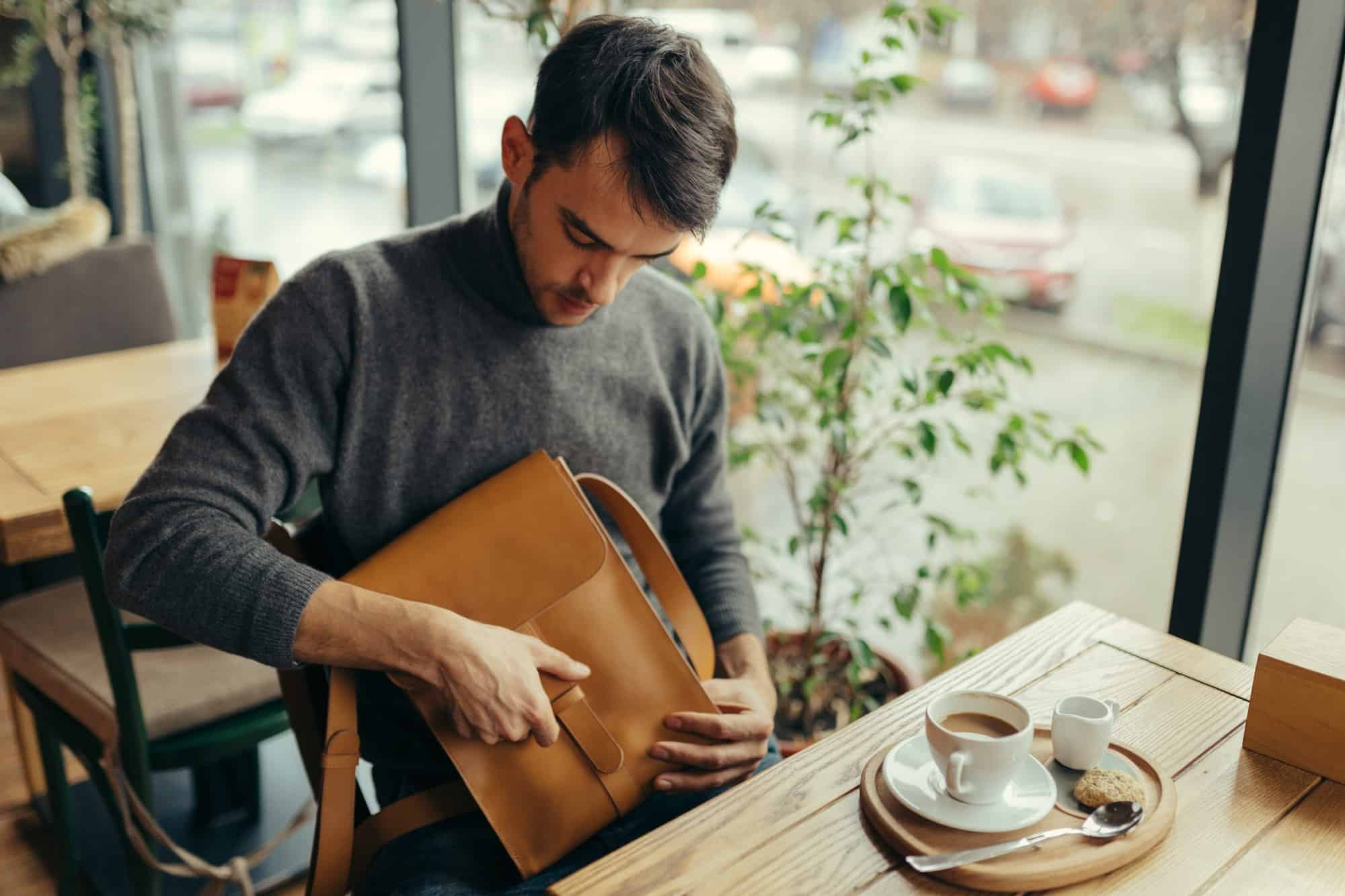 Handsome businessman with leather bag sitting at the table